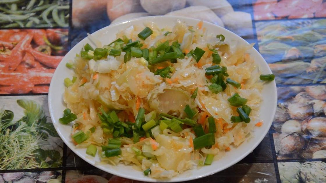 Квашеная капуста на тарелке с зеленью