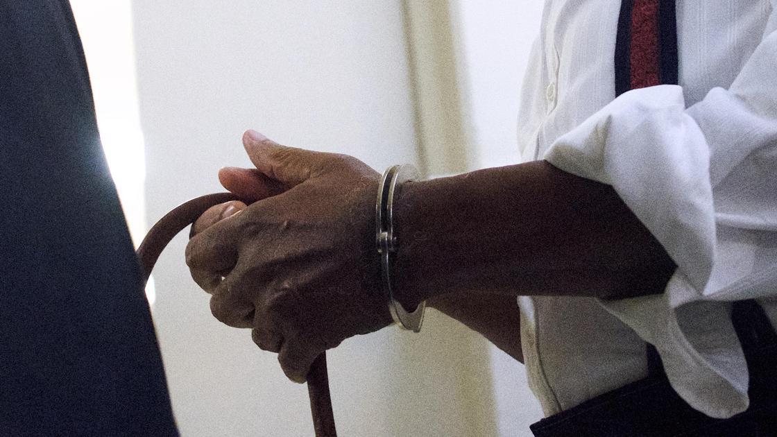 Мужчина держит в закованных в наручники руках трость