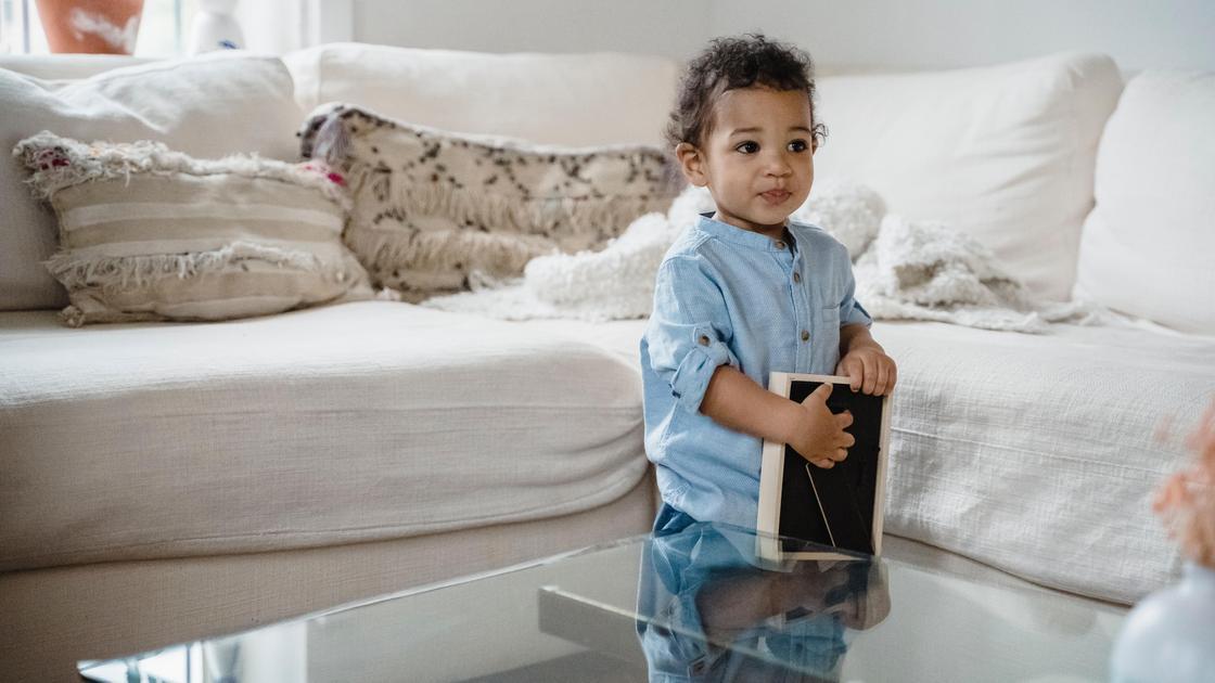 Ребенок стоит с книгой у стола