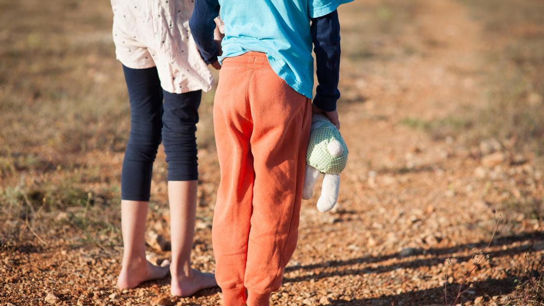 Два босых ребенка на земле стоят