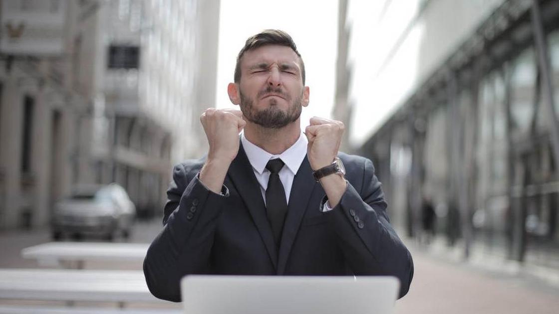 Мужчина в деловом костюме на улице с ноутбуком, сжав кулаки