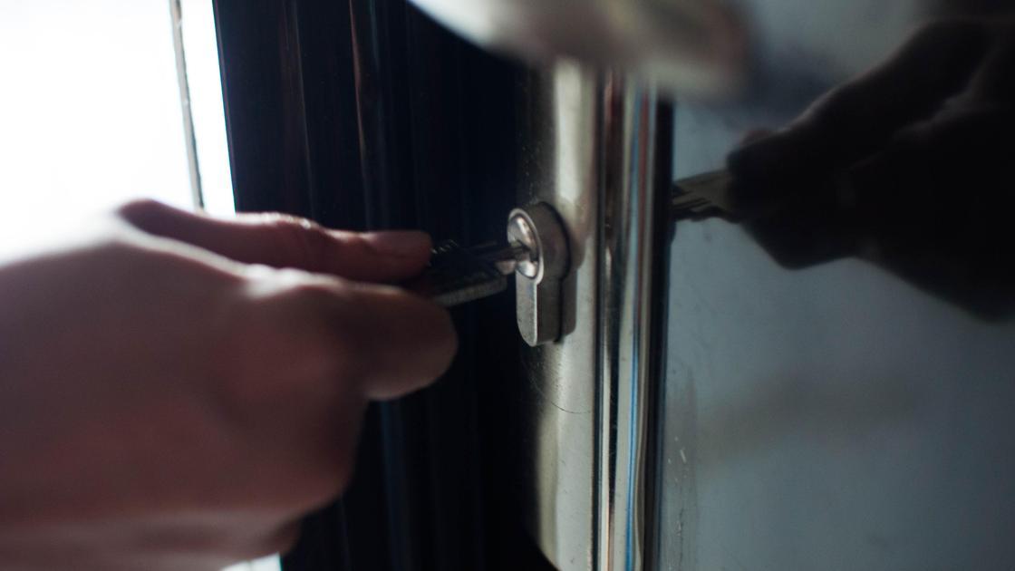 Человек открывает ключом дверь квартиры