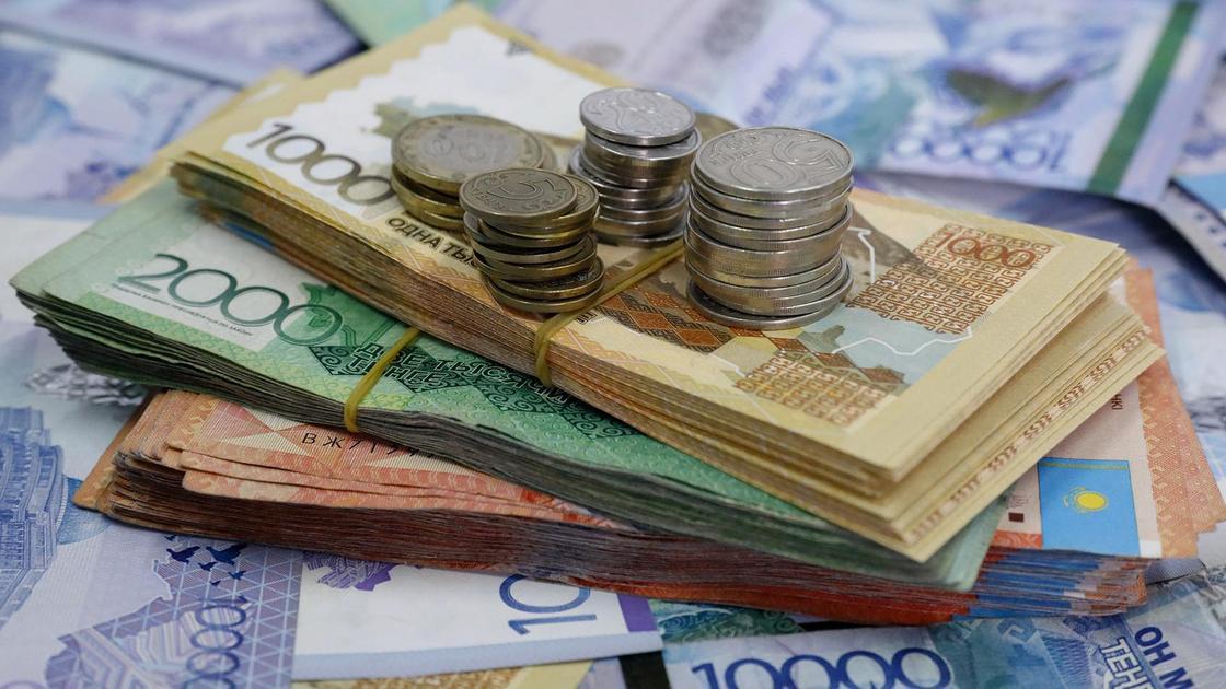 Купюры и монеты в тенге нескольких номиналов
