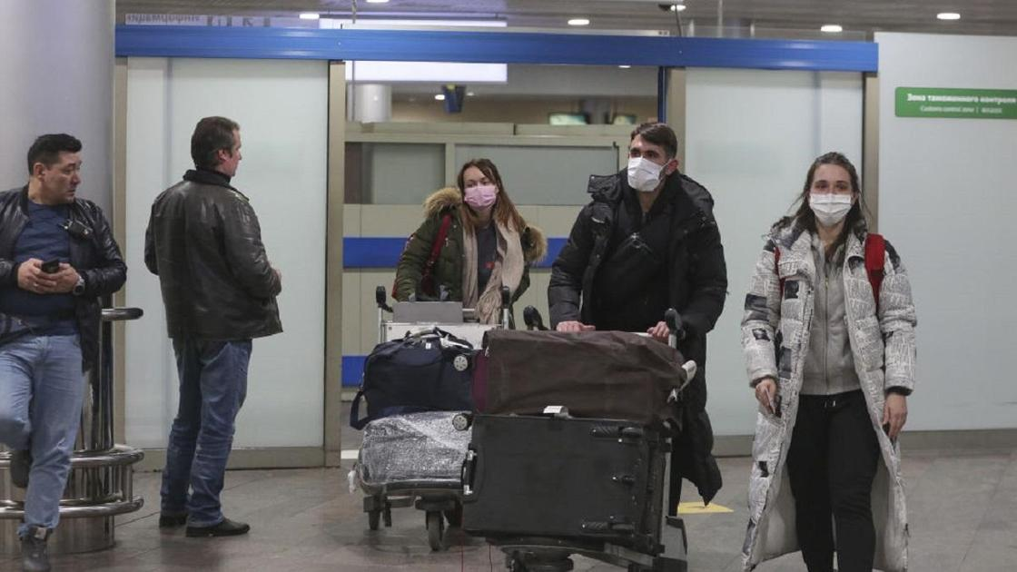 Пассажиры в масках везут багаж в аэропорту