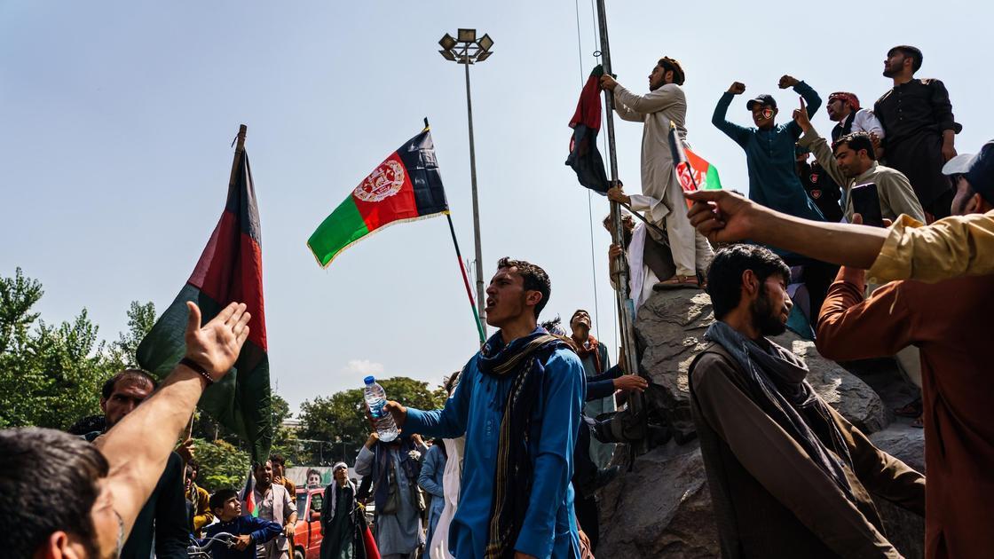 Мужчины держат флаг Афганистана