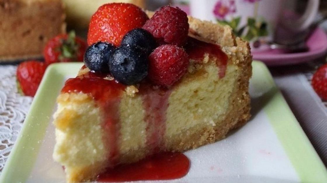 Кусочек творожного пирога, украшенного фруктами, на тарелке