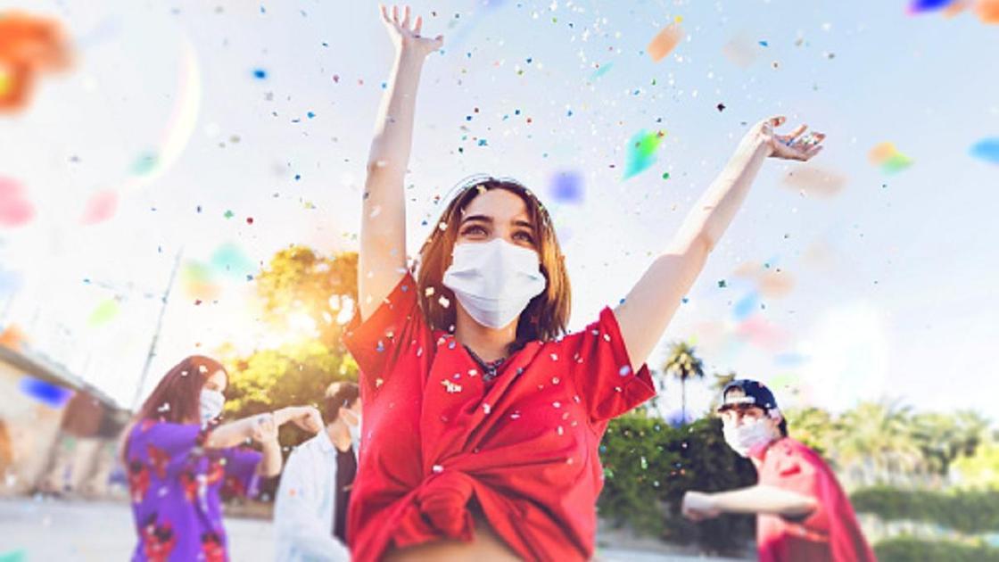 Женщина в маске радостно танцует на празднике