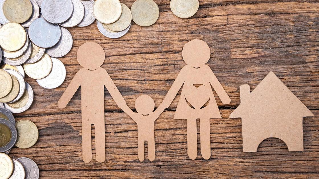 Фигурки членов семьи из картона лежат рядом с монетами