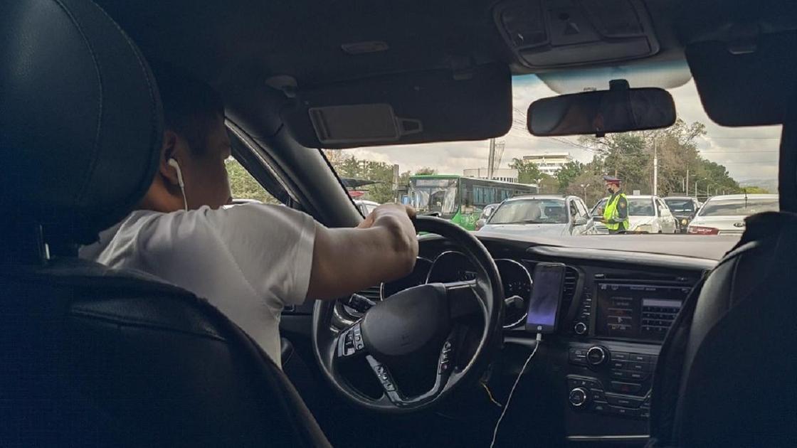 парень в наушниках сидит за рулем машины