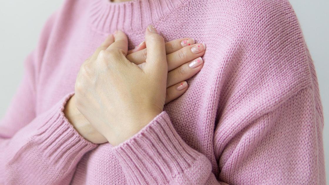 Девушка в розовом свитере держится за грудь