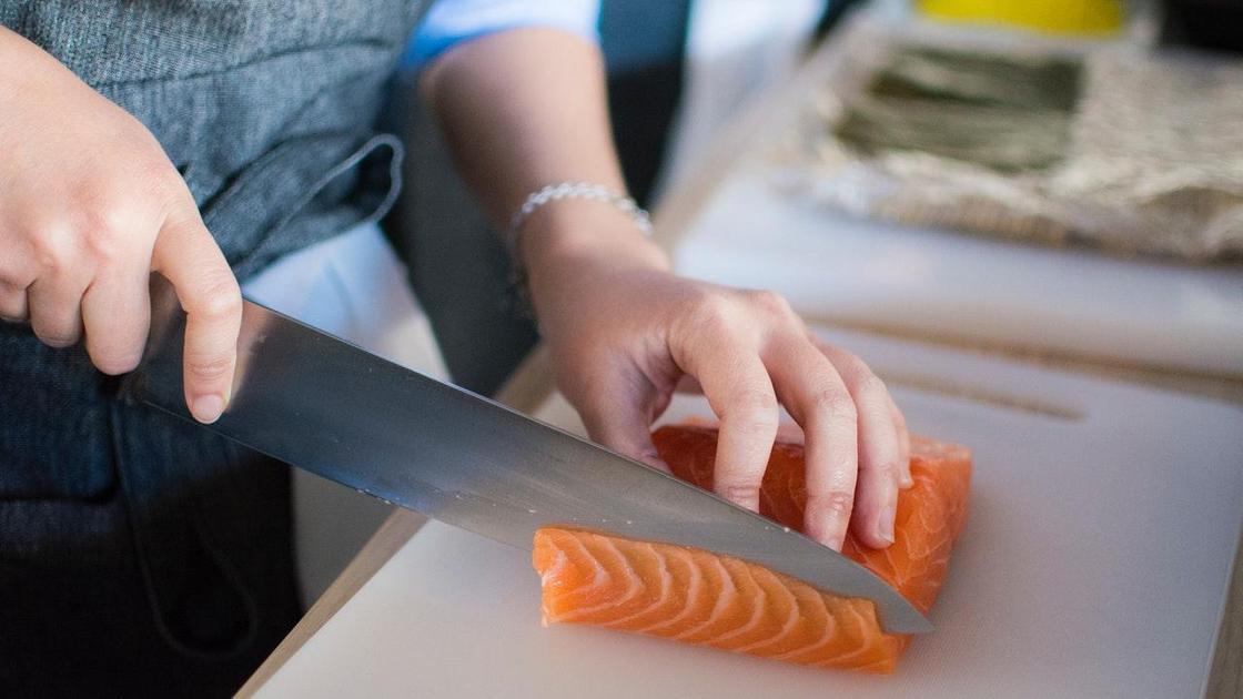 Повар нарезает рыбу ножом
