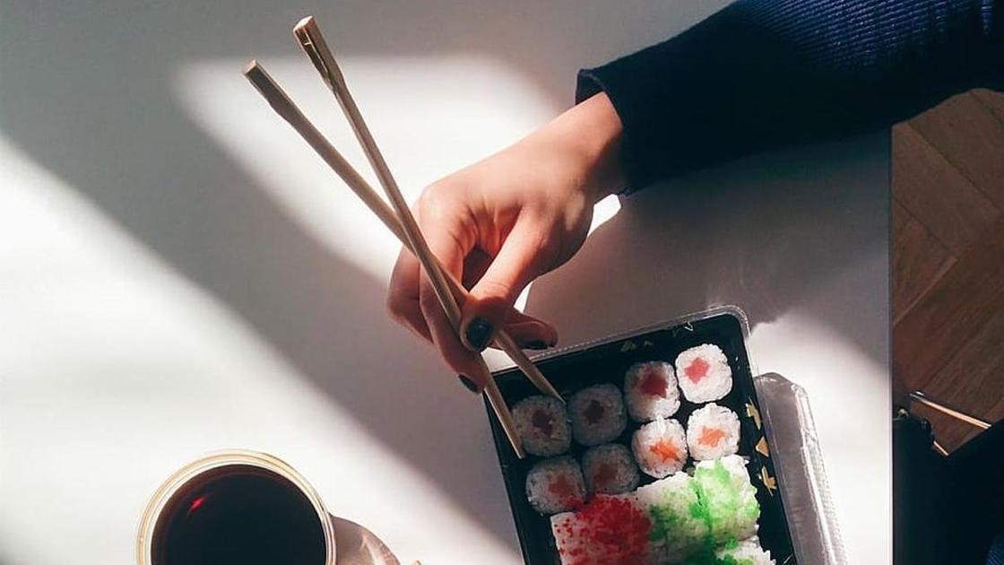 суши и рука, держащая палочки