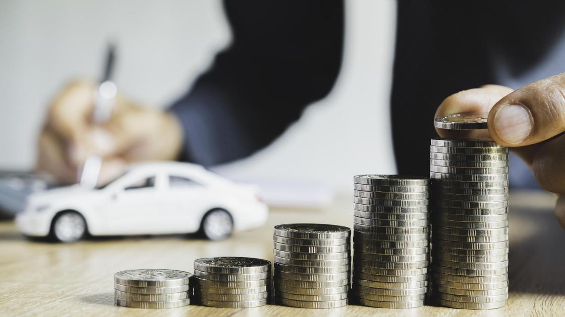 Мужчина подписывает договор о продаже автомобиля и считает деньги