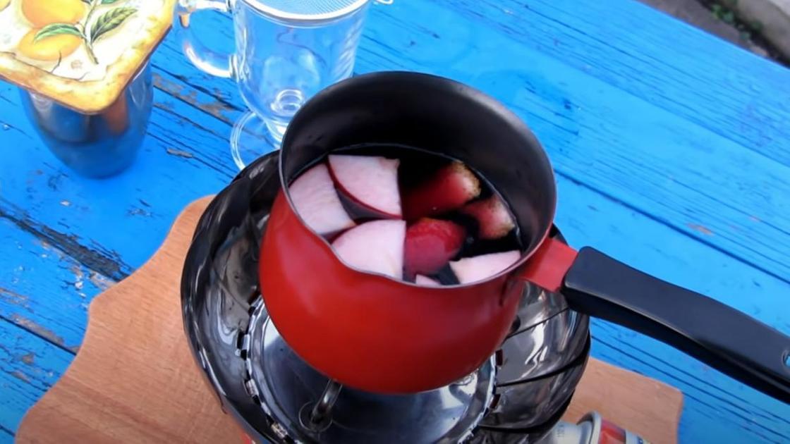 Яблоки, вино и апельсин в кастрюле