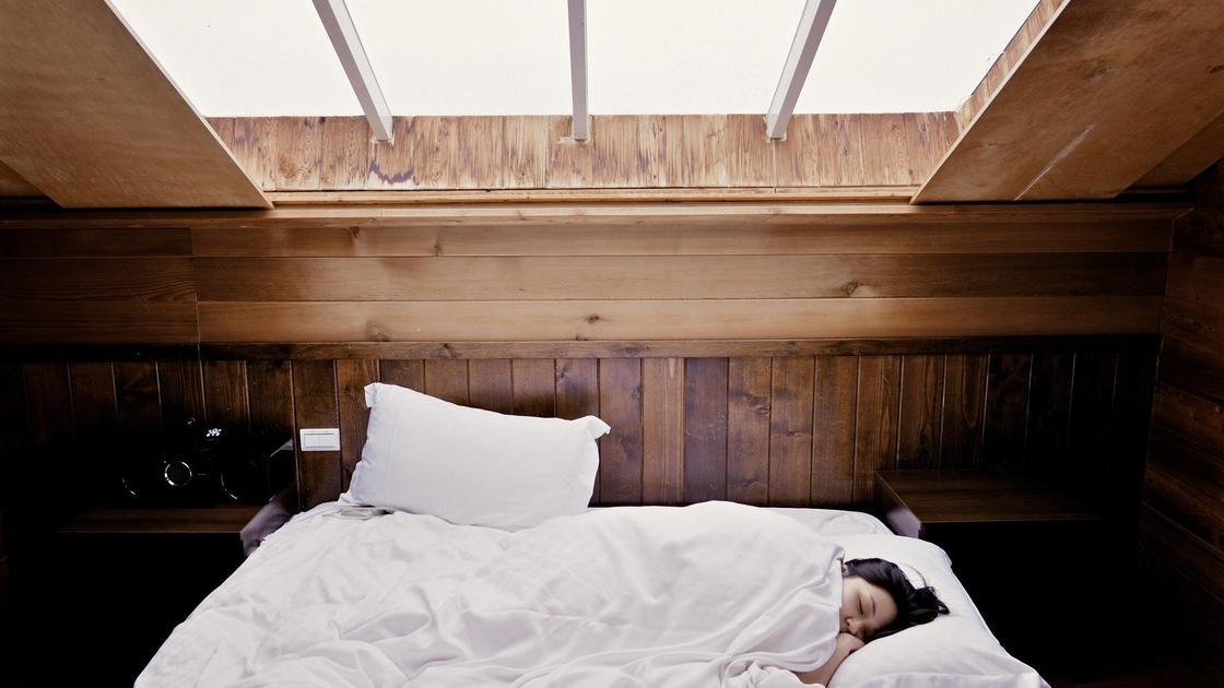 Девушка спит на белоснежной постели