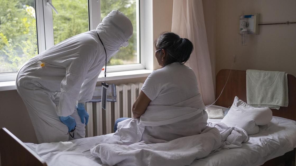 врач стоит возле пациентки в палате