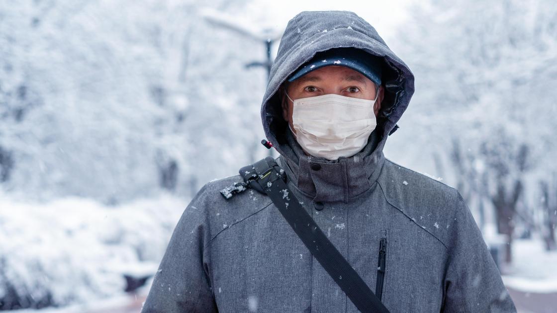 Мужчина в маске и в куртке с капюшоном стоит на зимней улице