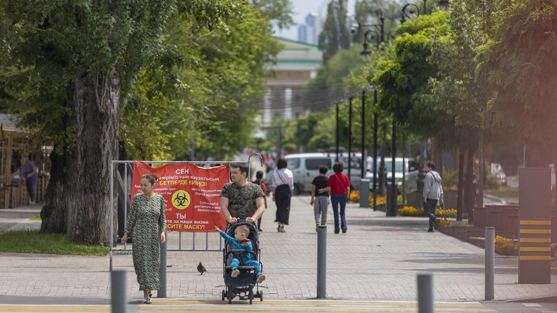 Женщина и мужчина с ребенком в коляске переходят дорогу