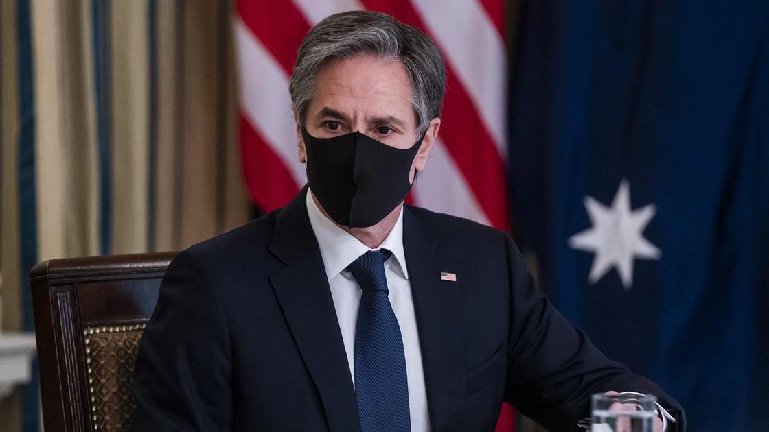 Госсекретарь США Энтони Блинкен в маске на фоне флага