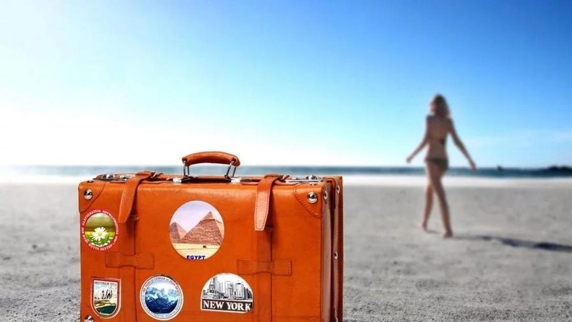 чемодан и пляж, по которому идет девушка