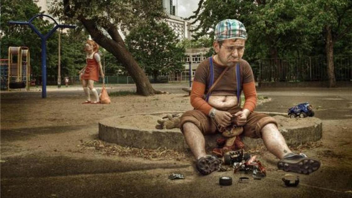 мужчина в образе ребенка на детской площадке