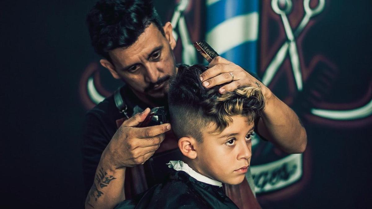 Мастер делает мальчику стрижку