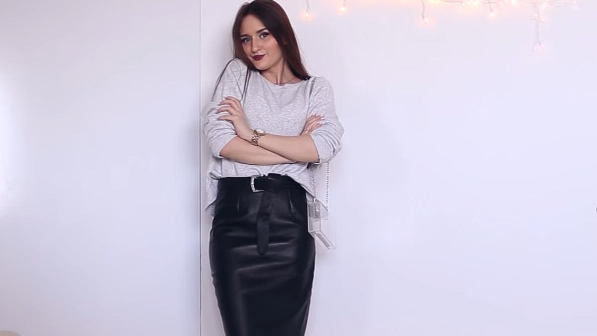 Девушка в кофте и кожаной юбке-карандаш черного цвета позирует