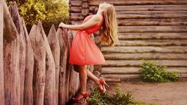 Девушка в коралловом платье около забора