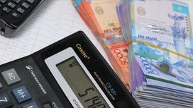 Калькулятор лежит на графике рядом с деньгами