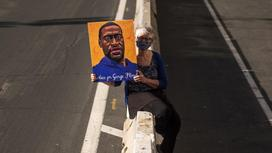 Женщина держит в руках картину Джорджа Флойда
