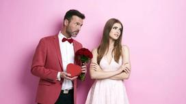 Мужчина дарит девушке конфеты и цветы