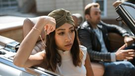 Мужчина и сердитая женщина сидят в автомобиле с открытым верхом