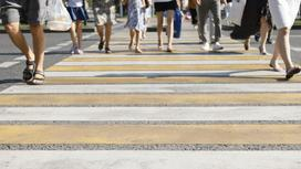 Люди переходят дорогу по пешеходному переходу