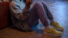 Девушка-подросток сидит на полу