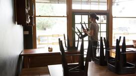 Официант поднимает стулья на столы в ресторане