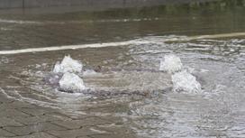 Вода вырывается из-под канализационного люка