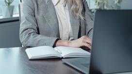 Женщина сидит за ноутбуком в офисе
