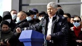 Алмазбек Атамбаев стоит перед трибуной в окружении людей