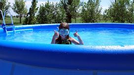 Девочка купается в бассейне