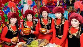 Девушки в национальных костюмах сидят за столом