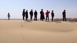 Несколько людей стоят на песчаном бархане