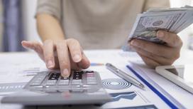 Женщина считает на калькуляторе, держа в руке долларовые купюры
