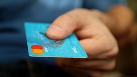 Мужчина держит в руке банковскую карту