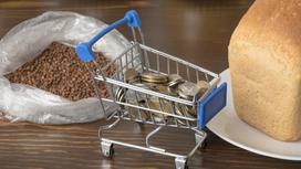 Маленькая корзина для продуктов наполнена монетами тенге и стоит рядом с хлебом и крупами