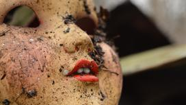 Кукла лежит в грязи