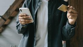 Парень держит телефон в руках