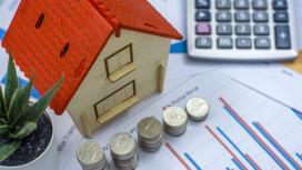 Модель жилого дома стоит рядом с монетами и калькулятором