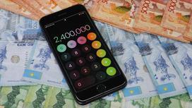 Телефон с открытым калькулятором лежит на деньгах