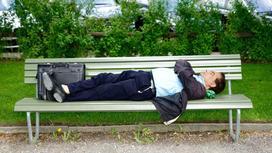 Мужчина лежит на скамейке в парке