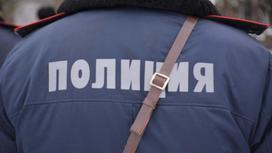 Полицейский в форме стоит спиной к фотографу